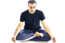 A man in a black t-shirt and blue yoga pants sitting in padmasana or lotus pose