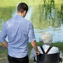 An elderly person on a wheelchair looking out to the lake with a male caregiver standing next to him