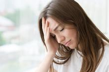 Image: Stock pic of woman with brunette hair holding her head during a migraine attack