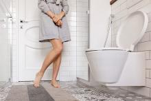 Stock image of a woman rushing to the toilet due to urgent and uncontrollable need to pee
