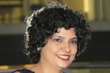 Head shot of Urvi Sabnis, a breast cancer survivor smiling at the camera