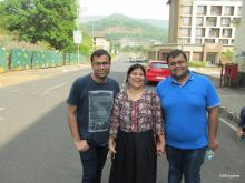 A mom in a printed top and black skirt flanked by her adult sons,  the one on the left with a dark t-shirt and the one on the right with a blue t-shirt. In the background is a red car parked in front of a building on the right and a fence and trees on the left
