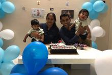 A couple with their kids on either side with a cake on the table in front and blue and white balloons around