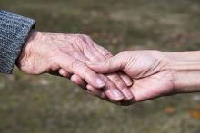 Image indicates a caregiver holding the hand of an older person