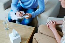A stock pic of partially visible person sitting in a consult session with a partially visible counsellor with a note book in her hand. In front of them is a table with a glass of water and a box of tissues