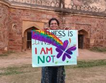Image: A woman stands with a poster showing her support for fibro warriors