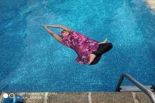 A woman in a pink swim suit doing yoga in a pool