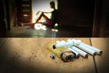 Image of a person sitting in a doorway and unused cigarettes on the table in the foreground depicting smoking or nicotine withdrawal