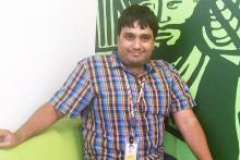 Image: Anirudh, autistic young man sitting in a checked shirt and sitting on a green sofa and a green background