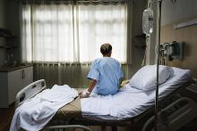 A man sitting in hospital gown on a hospital bed