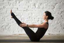 A woman in black leotards in a Half Boat Pose (Ardha Navasana)