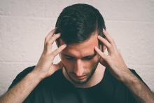 a man holding his head due to throbbing migraine headache