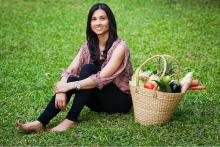 Priya sitting on a green patch with a basket of fresh food next to her sharing her management of hypothyroidism