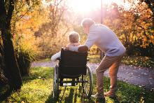 A couple, a woman on a wheel chair with a man standing attentively next to her, both looking into the woods with the sun streaming through