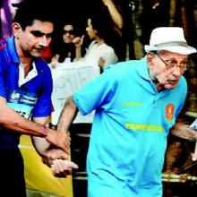 Parkinsons patient Merwan Zend in front in a light blue shirt and hat walking in front supported by another young man in a darker blue shirt