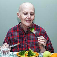A cancer patient, shown as bald due to chemotherapy eating food