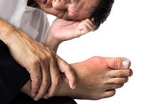 Image: A man looking at his foot which has gout symptoms