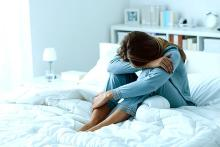 Image of a woman in blue trousers and a blue shirt in distress with head in her knees