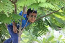 Omkar who has Congenital Adrenal Hyperplasia (CAH) climbing a tree