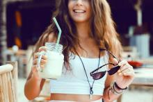 Image: A young lady in a summery white crop top, a cool drink with a straw in hand, dark glasses in the other hand