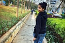 A young woman Shweta Chawre in a black sweater and jeans looking back at the camera as she walks away