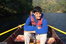 Image: Pranav, young autistic person on a boat in a river