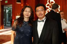 On the left is Yee Ling with her husband Yen-Lu Chow on the right. She is dressed in a black formal dress and he is wearing a black tuxedo with a white shirt. The background is red and shows some people blurred